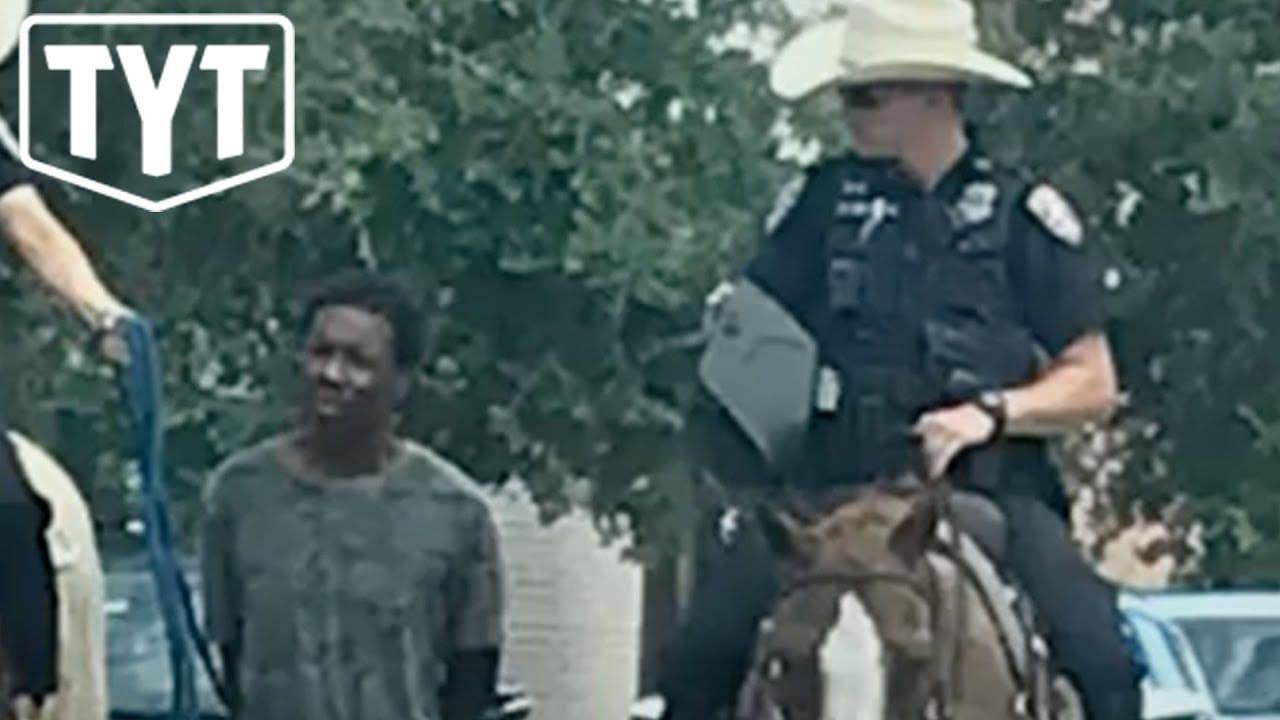 Photo of White Officers Walk Black Man Down The Street Like A Dog