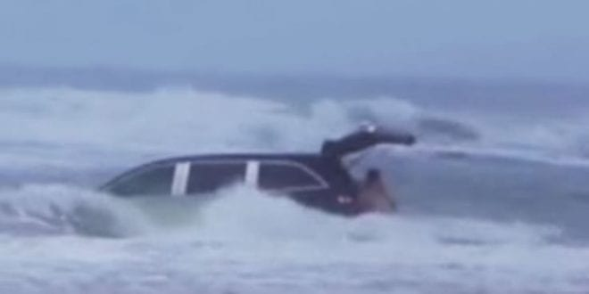 mother drives car in the ocean with kids