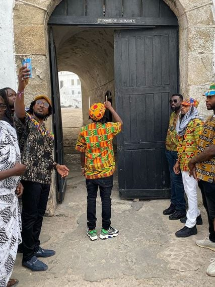 popcaan in ghana touring pointing up in the air